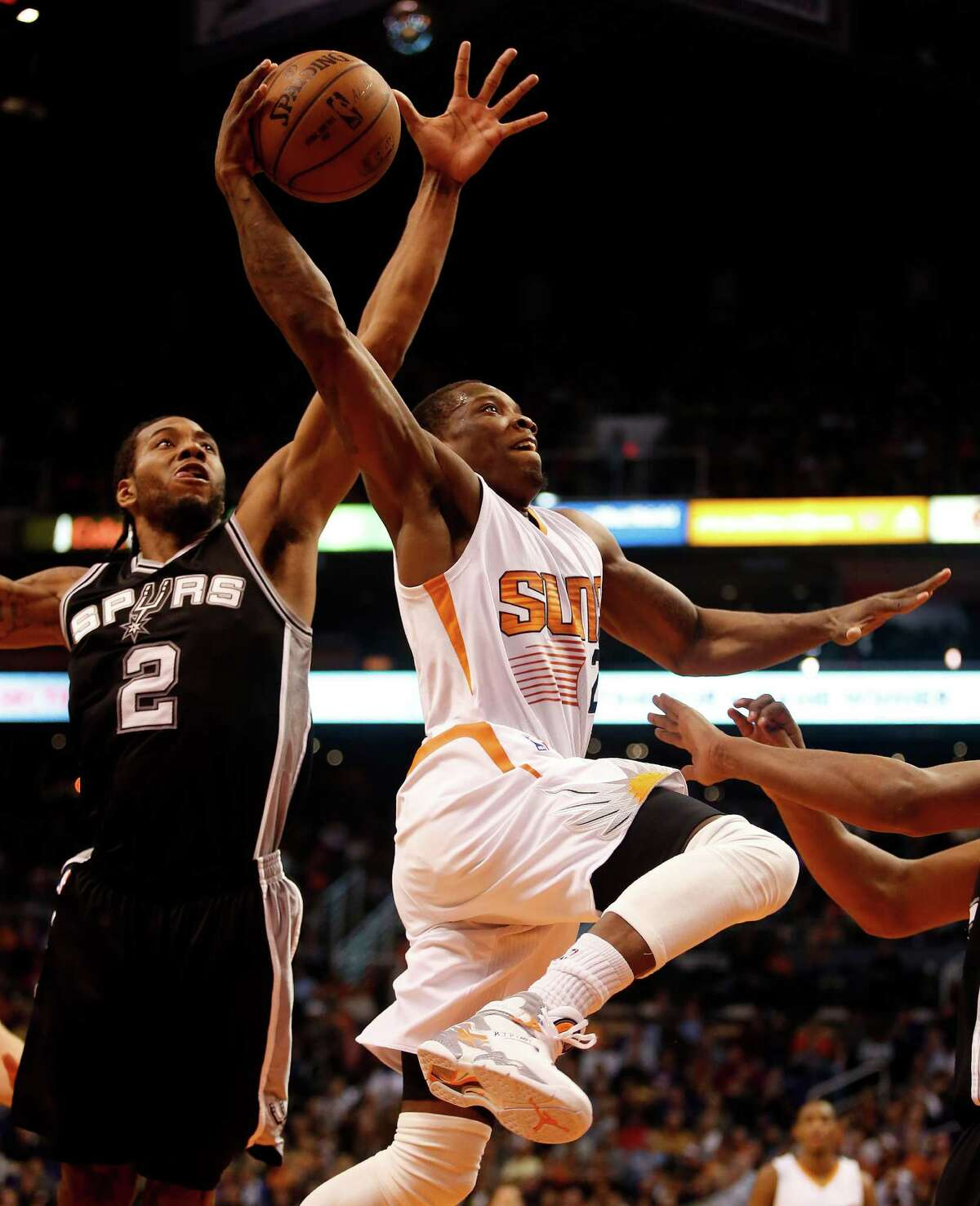 San Antonio Spurs forward Kawhi Leonard (2) blocks the shot on Phoenix Suns guard Eric Bledsoe (2) in the first quarter during an NBA basketball game, Saturday, Feb. 28, 2015, in Phoenix. (AP Photo/Rick Scuteri)
