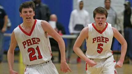 Fairfield Prep's #5 Thomas Nolan, center #21 Ryan Foley and #2 Matthew Gerics celebrate after a successfully offensive play during Monday evening SCC semifinals against Hamden High School.  Fairfield Prep would win 68-51.