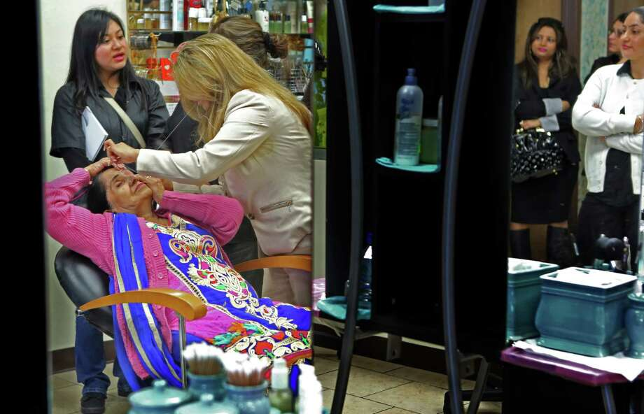 Sangeeta Dua, of India, owner of Apsara Beauty Center, threads the eyebrows of mother Sunita Dua to demonstrate threading technique to students on Sunday, Feb. 1, 2015, in Houston. Photo: Mayra Beltran, Houston Chronicle / © 2015 Houston Chronicle