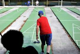 Larry Shaling, center, of Tampa, plays a game of shuffleboard with Steve Scott, bottom left, at MacFarlane Park, Monday, March 2, 2015, in Tampa, Fla. (AP Photo/The Tampa Bay Times, Octavio Jones)