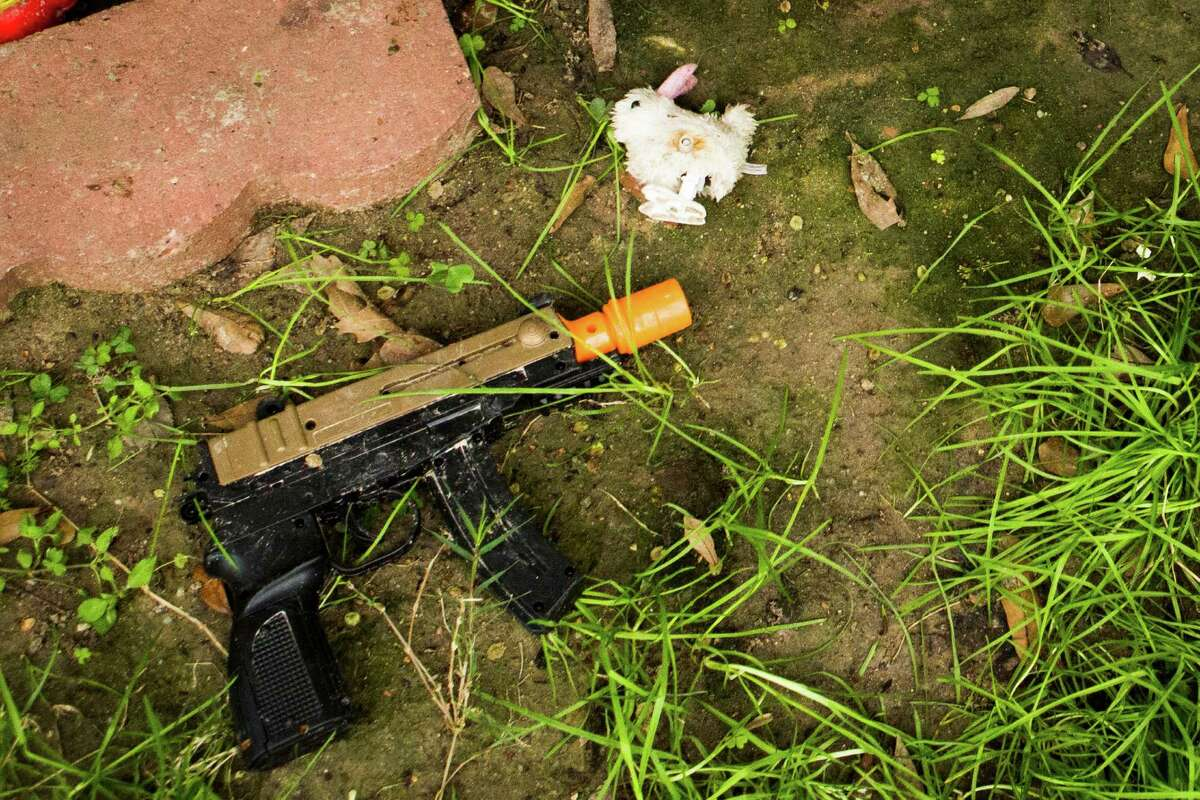 A toy gun lies in the front yard of a home where a 6-year-old boy was shot by his brother Monday.
