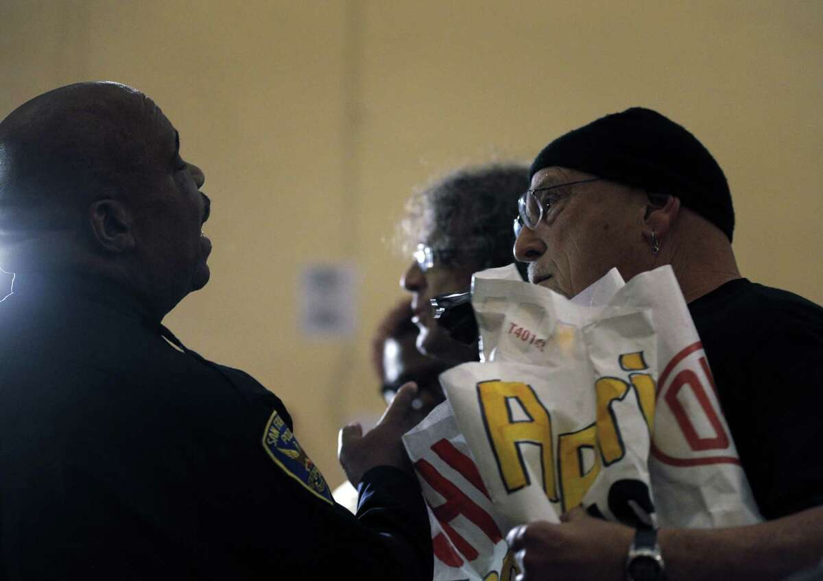 Deandre Teeter, right, speaks to a police officer to give his speaking time to Eddie Stiel, rear, during a town hall meeting on Monday, March 2, 2015, in San Francisco, Calif., to address the officer-involved shooting of Amilcar Perez-Lopez, who was killed the previous Thursday.