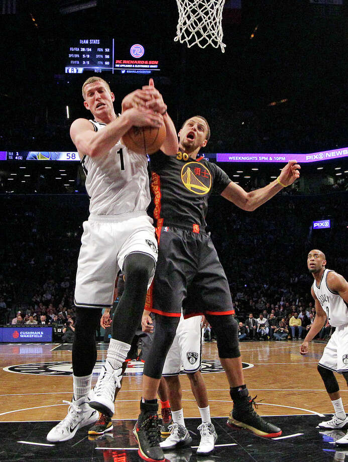 Stephen Curry takes a shot at stripping a rebound from Brooklyn center Mason Plumlee during the first half. Photo: Kathy Willens / Associated Press / AP