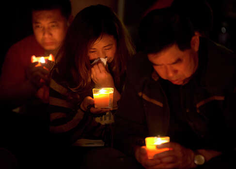 A woman, center, cries as she and others attend a candlelight vigil for their loved ones with other relatives of Chinese passengers onboard the missing Malaysia Airlines Flight 370 at a hotel in Beijing, China, Tuesday, April 8, 2014. An Australian ship detected two distinct, long-lasting sounds underwater that are consistent with the pings from aircraft black boxes in a major break in the month long hunt for the missing Malaysia Airlines jet, the search coordinator said Monday, April 7, 2014. (AP Photo/Andy Wong) Photo: Andy Wong, Associated Press / AP2014