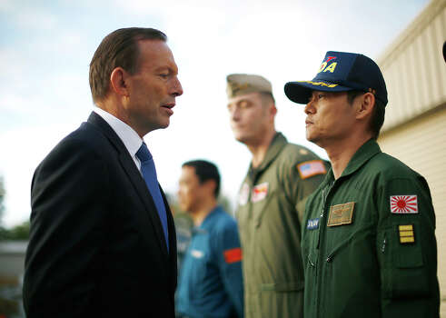 "Australian Prime Minister Tony Abbott speaks with Japan's Self Defense Force Commander Hidetsugu Iwamasa during his visit to RAAF Base Pearce where various forces are currently based as they search for the missing Malaysia Airlines Flight 370, in Bullsbrook near Perth, Australia, Monday, March 31, 2014. Abbott said the search for Malaysia Airlines Flight 370 is ""an extraordinarily difficult exercise"" but that it will go on as long as possible. Abbott said Monday that although no debris has been found in the southern Indian Ocean that can be linked to the plane missing for more than three weeks, the searchers are ""well, well short"" of any point where they would scale the hunt back. (AP Photo/Jason Reed, Pool) Photo: Jason Reed, Associated Press / REUTERS2014"