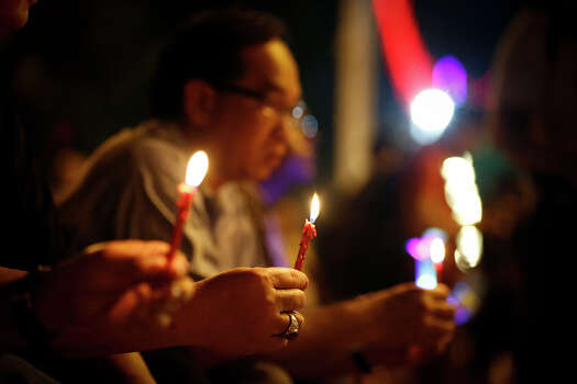 A man holds candles during a candlelight vigil for passengers onboard the missing Malaysia Airlines Flight MH370, in Kuala Lumpur, Malaysia, Monday, April 7, 2014. An Australian ship detected two distinct, long-lasting sounds underwater that are consistent with the pings from aircraft black boxes in a major break in the month long hunt for the missing Malaysia Airlines jet, the search coordinator said Monday. (AP Photo/Vincent Thian) Photo: Vincent Thian, Associated Press / AP