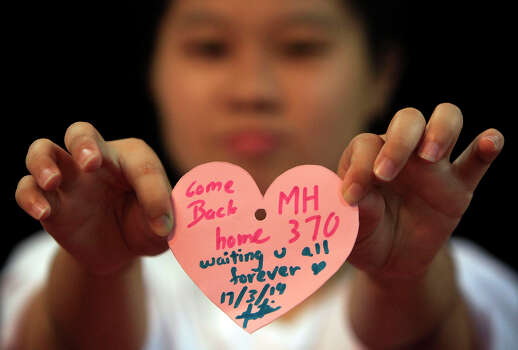 A woman holds a heart shaped paper with messages for passengers aboard a missing Malaysia Airlines plane, as she poses for a photo during an event in Kuala Lumpur, Malaysia, Monday, March 17, 2014. Authorities now believe someone on board the Boeing 777 shut down part of the aircraft's messaging system about the same time the plane with 239 people on board disappeared from civilian radar. But an Inmarsat satellite was able to automatically connect with a portion of the messaging system that remained in operation, similar to a phone call that just rings because no one is on the other end to pick it up and provide information. No location information was exchanged, but the satellite continued to identify the plane once an hour for four to five hours after it disappeared from radar screens. (AP Photo/Lai Seng Sin) Photo: Lai Seng Sin, Associated Press / AP2014