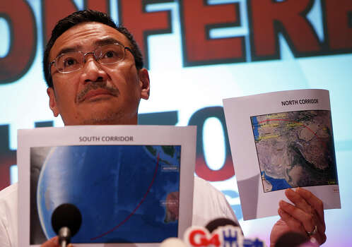 Malaysia's acting Transport Minister Hishamuddin Hussein shows maps of southern corridor and northern corridor of the search and rescue operation during a press conference at a hotel near the Kuala Lumpur International Airport, in Sepang, Malaysia, Monday, March 17, 2014. Twenty-six countries are involved in the massive international search for the Malaysia Airlines jetliner that disappeared on March 8 with 239 people aboard. They include not just military assets on land, at sea and in the air, but also investigators and the specific support and assistance requested by Malaysia, such as radar and satellite information. (AP Photo/Vincent Thian) Photo: Vincent Thian, Associated Press / AP2014