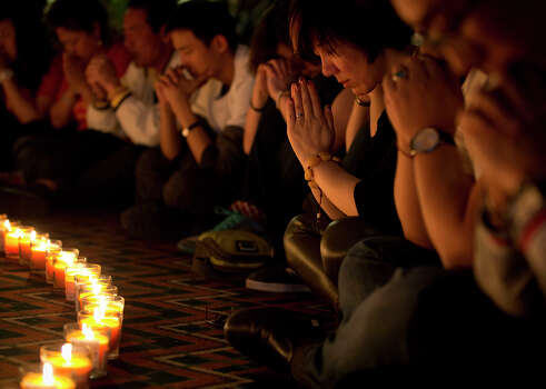 Relatives of Chinese passengers aboard Malaysia Airlines Flight 370 pray during a candlelight vigil for their loved ones at a hotel in Beijing, China, Tuesday, April 8, 2014. (AP Photo/Andy Wong) Photo: Andy Wong, Associated Press / AP2014