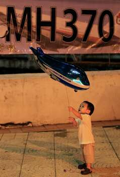 A boy plays with an aeroplane shaped foil balloon during a candlelight vigil for passengers aboard the missing Malaysia Airlines Flight MH370, in Kuala Lumpur, Malaysia, Sunday, April 6, 2014. Searchers hunting for the missing Malaysia Airlines jet were racing to a patch of the southern Indian Ocean on Sunday to determine whether a few brief sounds picked up by underwater equipment came from the plane's black boxes, whose battery-operated beacons are on the verge of dying out. (AP Photo/Lai Seng Sin) Photo: Lai Seng Sin, Associated Press / AP