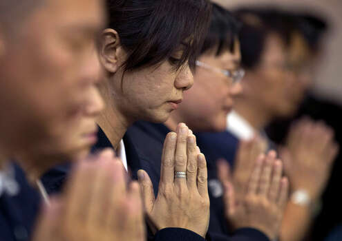 Volunteers from Taiwan's Buddhist association offer prayers for the Chinese passengers aboard the missing Malaysia Airlines flight MH370, at a hotel in Beijing, China Tuesday, April 1, 2014. Although it has been slow, difficult and frustrating so far, the search for the missing Malaysia Airlines jet is nowhere near the point of being scaled back, Australia's Prime Minister Tony Abbott said. The three-week hunt for Flight 370 has turned up no sign of the Boeing 777, which vanished March 8 with 239 people bound for Beijing from Kuala Lumpur. (AP Photo/Andy Wong) Photo: Andy Wong, Associated Press / AP2014