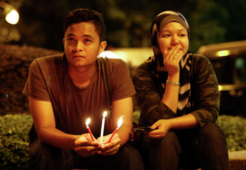 A Malaysian couple hold candles during a candlelight vigil for passengers onboard the missing Malaysia Airlines Flight MH370, in Kuala Lumpur, Malaysia, Monday, April 7, 2014. An Australian ship detected two distinct, long-lasting sounds underwater that are consistent with the pings from aircraft black boxes in a major break in the month long hunt for the missing Malaysia Airlines jet, the search coordinator said Monday. (AP Photo/Vincent Thian) Photo: Vincent Thian, Associated Press / AP2014