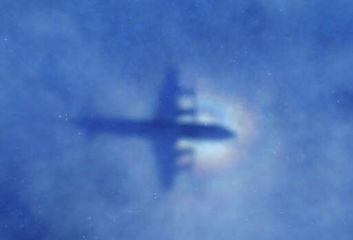 In this March 31, 2014 file photo, a shadow of a Royal New Zealand Air Force P-3 Orion aircraft is seen on low cloud cover while it searches for missing Malaysia Airlines Flight MH370 in the southern Indian Ocean.  From the disappearances of aviator Amelia Earhart to labor union leader Jimmy Hoffa, there's just something about a good mystery that Americans find too tantalizing to resist. Perhaps that's why the saga of missing Malaysia Airlines Flight 370 has continued to rivet the country long after people elsewhere have moved on.  (AP Photo/Rob Griffith, File) Photo: Rob Griffith, Associated Press / AP