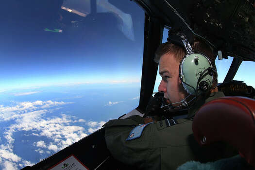 RAAF Flight Lieutenant Russell Adams looks out from the cockpit of an AP-3C Orion whilst on a search mission in the Southern Indian Ocean on March 26, 2014 in Perth, Australia. The search for flight MH370 resumes today after rough winds and high swells prevented crews from searching for debris yesterday. Six countries have joined the search, now considered to be a recovery effort, after authorities have announced that the airliner crashed in the Southern Indian Ocean and that there are no survivors. Photo: Paul Kane, Getty / 2014 Getty Images