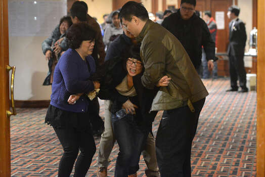 Grieving relatives of passengers on Malaysia Airlines flight MH370 leave a hotel hall at after being told the news that the plane plunged into Indian Ocean in Beijing on March 24, 2014.  The missing Malaysia Airlines jet came down in the Indian Ocean, Prime Minister Najib Razak said March 24, as the airline reportedly told relatives it had been lost and that none on board survived. Photo: GOH CHAI HIN, Getty / 2014 AFP
