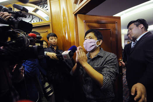 A man wearing a mask, who claimed to be a relative of a passenger from the missing Malaysia Airlines flight MH370, speaks to the media outside the lounge in Beijing on March 14, 2014. Malaysia confirmed on March 14 that the search for a missing Malaysia Airlines plane had been expanded into the Indian Ocean, but declined to comment on US reports that the jet had flown for hours after going missing. Photo: WANG ZHAO, Getty / 2014 AFP