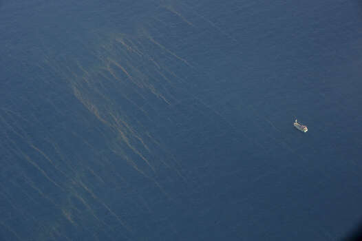 This aerial picture taken from aboard a flying Soviet-made AN-26 used as a search aircraft by Vietnamese Air Force to look for missing Malaysia Airlines flight MH370, shows a boat (R) sailing past oil spills (L) on the surface of the water off the southern seas of Vietnam on March 9, 2014. Malaysia on March 9 launched a terror probe into the disappearance of a Malaysian Airlines passenger jet carrying 239 people the day before, investigating suspect passengers who boarded with stolen passports, as relatives begged for news of their loved ones. The United States sent the FBI to investigate after Malaysia Airlines flight MH370 vanished from radar early on March 8 somewhere at sea between Malaysia and Vietnam, but stressed there was no evidence of terrorism yet. Photo: HOANG DINH NAM, Getty / 2014 AFP