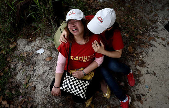 "Relatives of Chinese passengers from the missing Malaysia Airlines flight MH370, console each other outside the Malaysia Airlines office in Subang on the outskirts of Kuala Lumpur on February 12, 2015.  Chinese relatives of passengers on missing flight MH370 protested outside the Malaysian Airlines office demanding Malaysia withdraw the statement that all the passengers are dead. About 15 people gathered outside the gates wearing white caps and red t-shirts with words: ""Pray for MH370.""   AFP PHOTO / MANAN VATSYAYANA Photo: MANAN VATSYAYANA, Getty / AFP"
