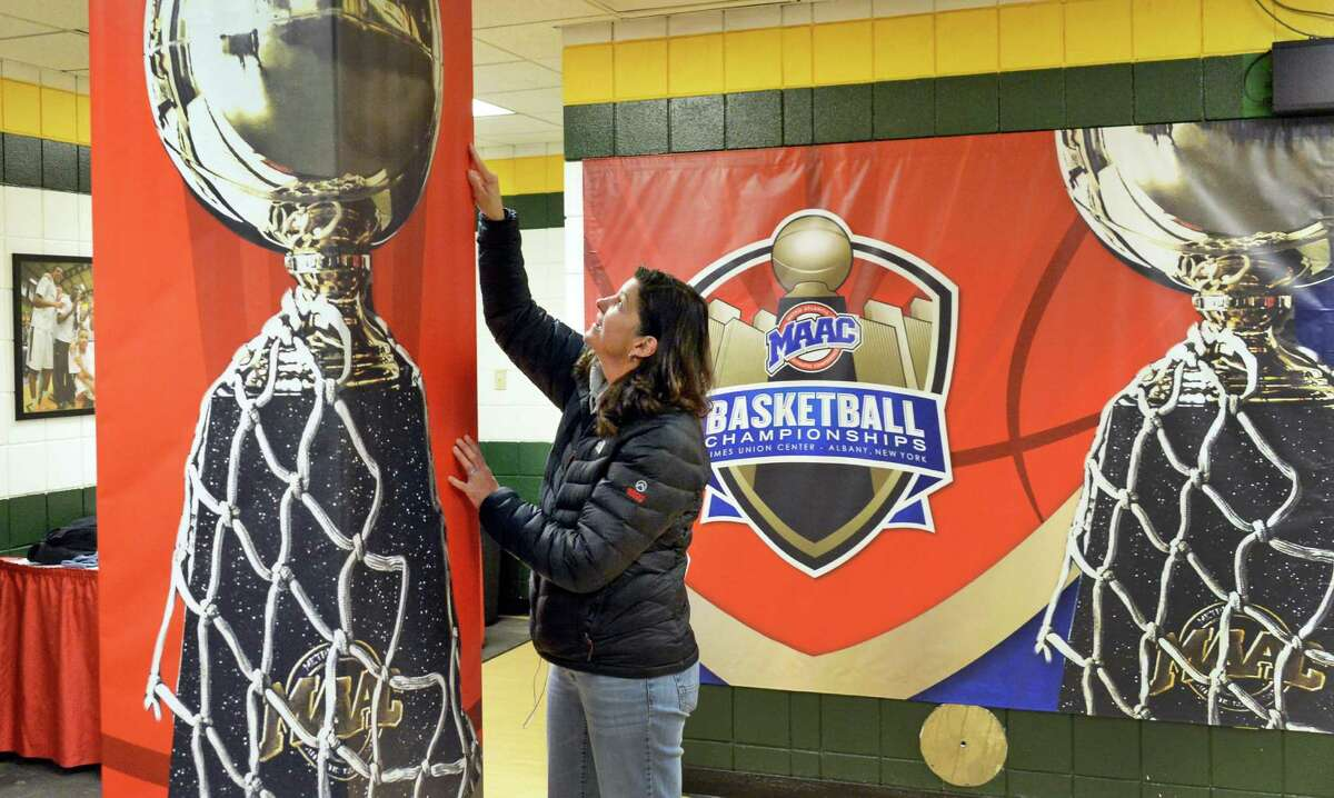 MAAC staffer Michelle Perry finishes up graphics in a team locker room for the upcoming MAAC basketball tournament at the Times Union Center Tuesday, March 3, 2015, in Albany, N.Y. (John Carl D'Annibale / Times Union)