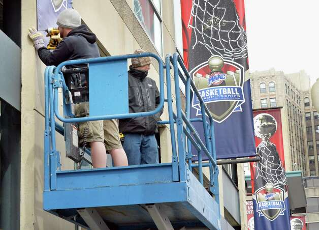 Nick Slowikowski, left, and Jason Potter of Sports Graphic hang banners outside the Times Union Center for the MAAC basketball tournament Tuesday, March 3, 2015, in Albany, N.Y. (John Carl D'Annibale / Times Union) Photo: John Carl D'Annibale / 10030844A