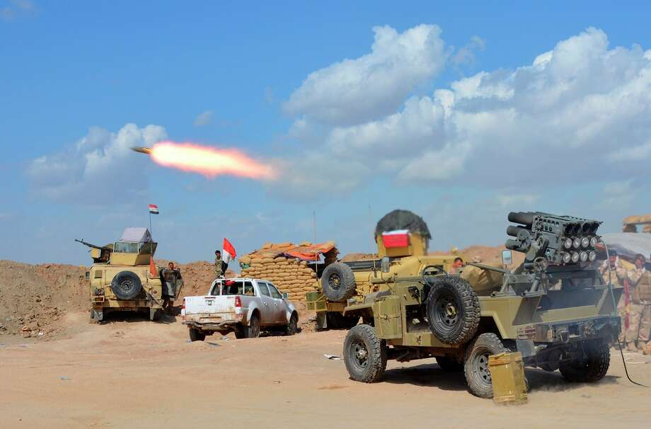 Iraqi government forces and allied militias fire weaponry, as they take part in an assault to retake the city of Tikrit from Islamic State fighters. Photo: YOUNIS AL-BAYATI / AFP / Getty Images / AFP