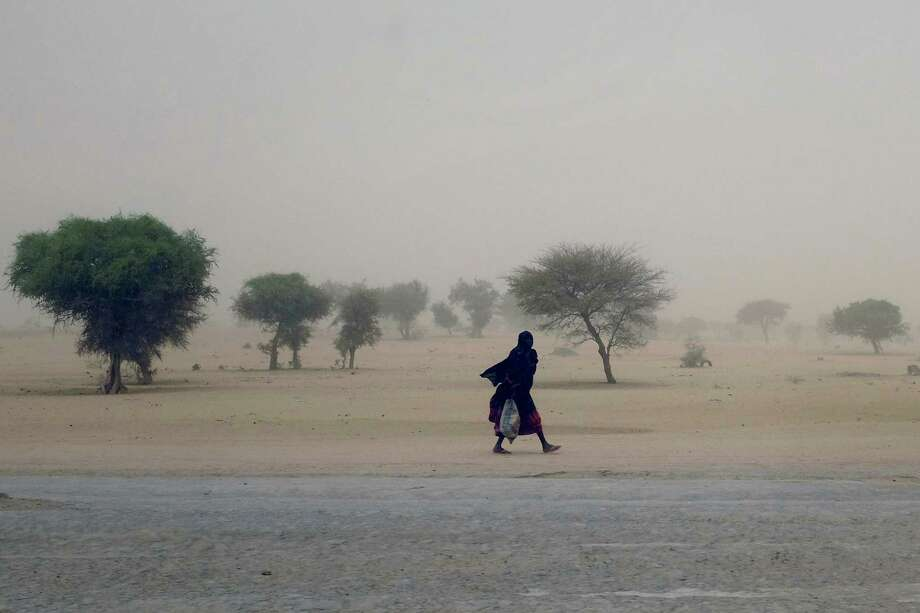 A woman walks in a sand storm near Lake Chad, in Chad. Chadian troops seized a strategically located northeast Nigerian town from Boko Haram, but not before the defeated Islamic extremists killed hundreds of civilians, Photo: Jerome Delay / Associated Press / AP