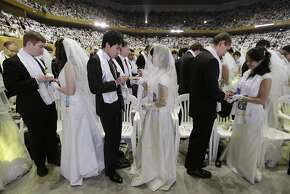 Couples from around the world exchange their rings in a mass wedding ceremony at the Cheong Shim Peace World Center in Gapyeong, South Korea, Tuesday, March 3, 2015. 3,800 couples from more than fifty countries exchanged or reaffirmed marriage vows in the Unification Church's mass wedding arranged by Hak Ja Han Moon, wife of the late Rev. Sun Myung Moon, the controversial founder of the church. (AP Photo/Ahn Young-joon)