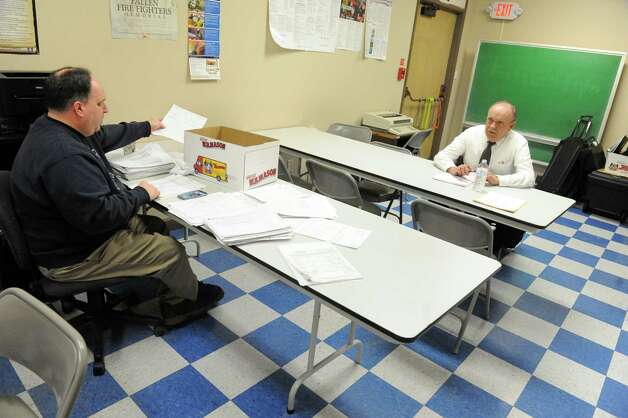 Mayor George Primeau, right, and City Comptroller Mike Durocher work out of a room at the Raymond K. Lamora Island Fire Station on Tuesday March 3, 2015 in Cohoes, N.Y. Cohoes City Hall is closed. Operations were moved to the fire station several blocks to the east while asbestos test results are waited to come back.(Michael P. Farrell/Times Union) Photo: Michael P. Farrell / 00030837A