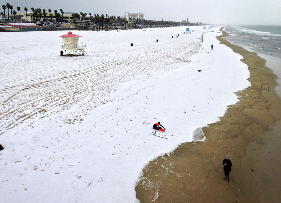 A surfer gets ready to head into the water as a blanket of hail covers the beach south of the Huntington Beach pier, Photo: Allen J. Schaben / McClatchy-Tribune News Service / Los Angeles Times