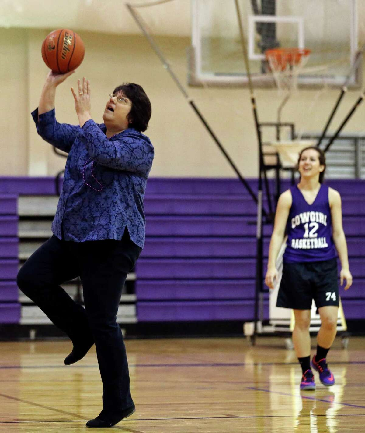 Annette Nester-Vordenbaum, a member of the 1979 D'Hanis Cowgirls basketball team, shoots as current team member Sarah Craft looks on during practice on March 2, 2015, in D'Hanis.