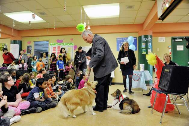 Terry Brown and his two dogs, Ziggy, left, and Jenna visit with children at Franklin D. Roosevelt Elementary School during an award ceremony for Brown on Tuesday, March 3, 2015, in Schenectady, N.Y.  Brown was awarded a Daily Point of Light award for his volunteer work with his two shelties, Ziggy and Jenna.  Brown and his dogs lead reading programs for children at local schools.  The national award for volunteers originated out of the White House in 1989 under former President George H.W. Bush.   (Paul Buckowski / Times Union) Photo: PAUL BUCKOWSKI / 00030814A