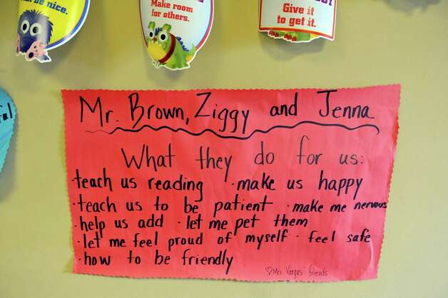 A sign is see on the wall at Franklin D. Roosevelt Elementary School during an award ceremony for Terry  Brown on Tuesday, March 3, 2015, in Schenectady, N.Y.  Brown was awarded a Daily Point of Light award for his volunteer work with his two shelties, Ziggy and Jenna.  Brown and his dogs lead reading programs for children at local schools.  The national award for volunteers originated out of the White House in 1989 under former President George H.W. Bush.   (Paul Buckowski / Times Union) Photo: PAUL BUCKOWSKI / 00030814A