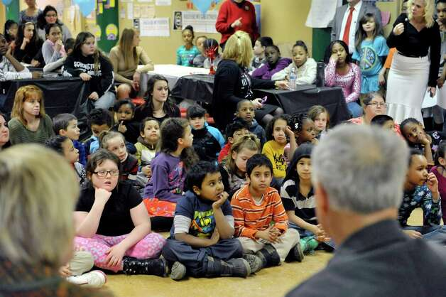 Children at Franklin D. Roosevelt Elementary School gather for an award ceremony for Terry Brown, foreground right, on Tuesday, March 3, 2015, in Schenectady, N.Y.  Brown was awarded a Daily Point of Light award for his volunteer work with his two shelties, Ziggy and Jenna.  Brown and his dogs lead reading programs for children at local schools.  The national award for volunteers originated out of the White House in 1989 under former President George H.W. Bush.   (Paul Buckowski / Times Union) Photo: PAUL BUCKOWSKI / 00030814A