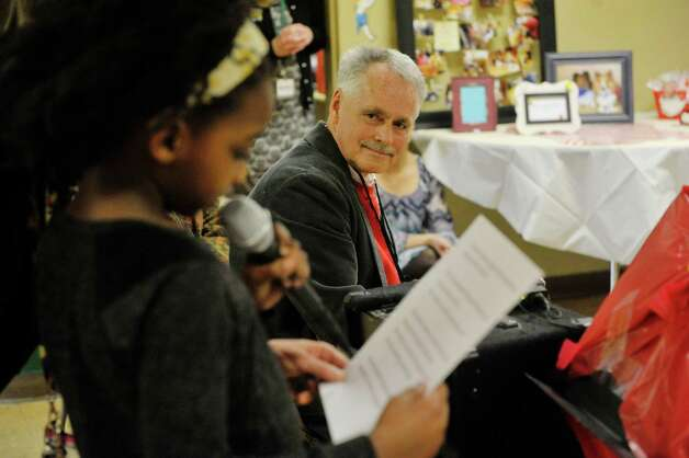 Tyana Camara, 7, a student at Franklin D. Roosevelt Elementary School, reads a letter about how Terry Brown, background, has helped her to read during an award ceremony for Brown on Tuesday, March 3, 2015, in Schenectady, N.Y.  Brown was awarded a Daily Point of Light award for his volunteer work with his two shelties, Ziggy and Jenna.  Brown and his dogs lead reading programs for children at local schools.  The national award for volunteers originated out of the White House in 1989 under former President George H.W. Bush.   (Paul Buckowski / Times Union) Photo: PAUL BUCKOWSKI / 00030814A
