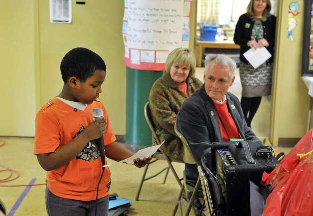 Malik Powell, left, 8, a student at Franklin D. Roosevelt Elementary School, reads a letter about how Terry Brown, right, has helped him to read during an award ceremony for Brown on Tuesday, March 3, 2015, in Schenectady, N.Y.  Also pictured is Brown's wife Regina Brown, center.  Brown was awarded a Daily Point of Light award for his volunteer work with his two shelties, Ziggy and Jenna.  Brown and his dogs lead reading programs for children at local schools.  The national award for volunteers originated out of the White House in 1989 under former President George H.W. Bush.   (Paul Buckowski / Times Union) Photo: PAUL BUCKOWSKI / 00030814A