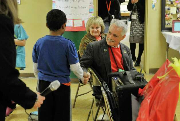 Ryan Dhanraj, left, 8, a student at Franklin D. Roosevelt Elementary School, shakes hands with Terry Brown, right, and his wife Regina Brown, center, during an award ceremony for Brown on Tuesday, March 3, 2015, in Schenectady, N.Y.  Brown was awarded a Daily Point of Light award for his volunteer work with his two shelties, Ziggy and Jenna.  Brown and his dogs lead reading programs for children at local schools.  The national award for volunteers originated out of the White House in 1989 under former President George H.W. Bush.   (Paul Buckowski / Times Union) Photo: PAUL BUCKOWSKI / 00030814A