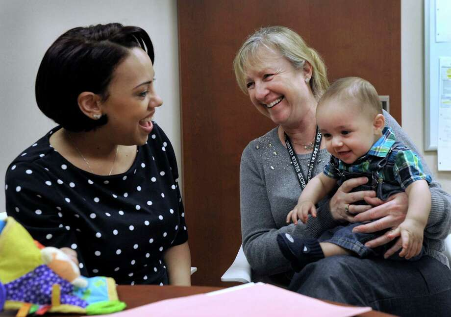 Sherrie Ruschmeyer, of Brookfield, Conn., holds Jude, the six-month-old son of Crystal Johnston, 30, left, of Danbury, Conn., Monday, March 2, 2015. Ruschmeyer is a doula with Danbury Hospital's Doula Program and assisted during the birth of Jude. Photo: Carol Kaliff / The News-Times