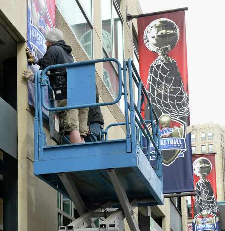 Nick Slowikowski of Sports Graphic hangs banners outside the Times Union Center for the MAAC tournament Tuesday March 3, 2015 in Albany, NY. (John Carl D'Annibale / Times Union) Photo: John Carl D'Annibale / 10030844A