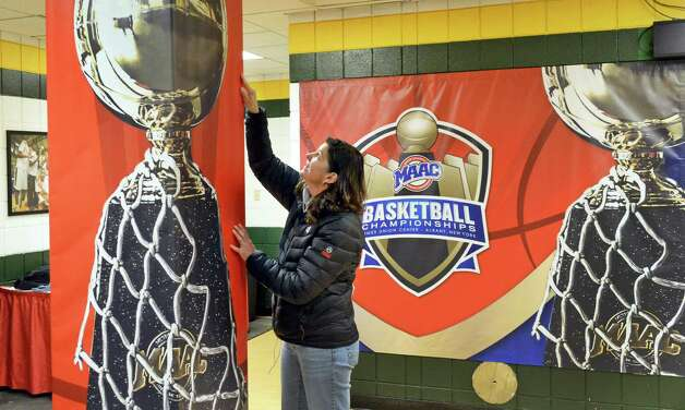 MAAC staffer Michelle Perry finishes up graphics in a team locker room for the upcoming MAAC tournament at the Times Union Center Tuesday March 3, 2015 in Albany, NY. (John Carl D'Annibale / Times Union) Photo: John Carl D'Annibale / 10030844A