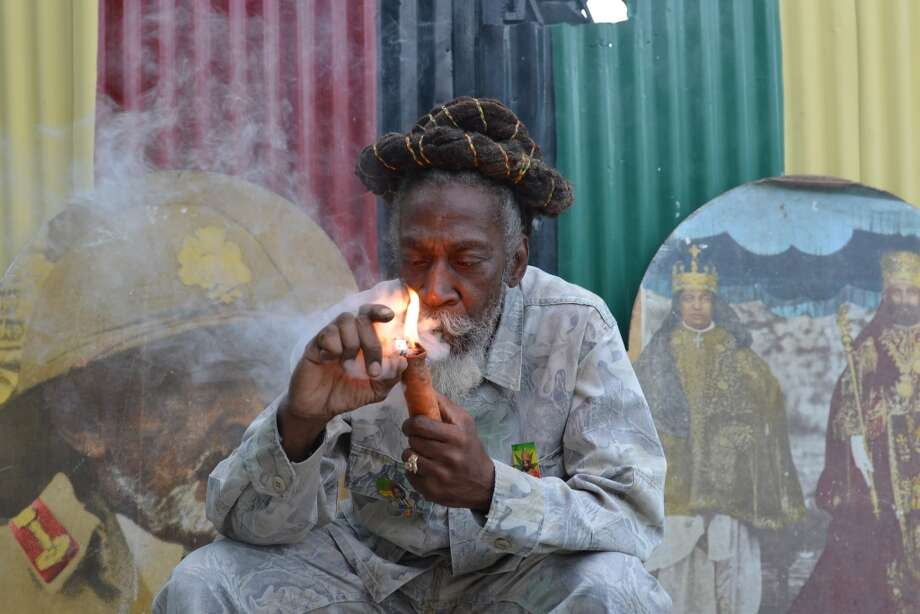 "Jamaica lawmakers on Feb. 24, 2015, passed an act to decriminalize small amounts of pot and establish a licensing agency to regulate a lawful medical marijuana industry on the island.  In this Aug. 28, 2014 file photo, legalization advocate and reggae legend Bunny Wailer smokes a pipe stuffed with marijuana during a ""reasoning"" session in a yard in Kingston, Jamaica. Photo: David McFadden, AP"