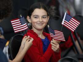 Francesca Nicosia, 10, waves U.S. flags before her father Paolo becomes an American citizen during a naturalization ceremony at the Rosie the Riveter National Historic Park in Richmond, Calif. on Tuesday, March 3, 2015. Forty-one immigrants representing 27 countries were sworn-in as the nation's newest citizens.