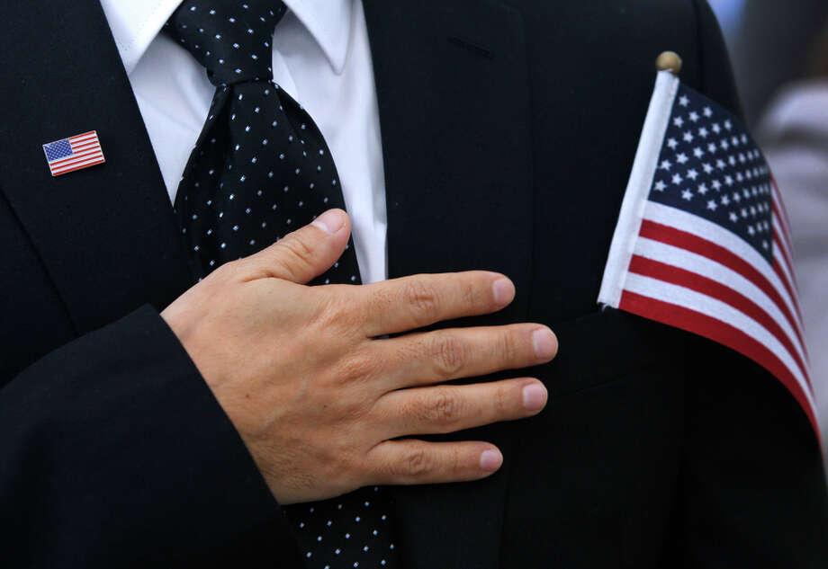 Nelson Castro recites the Pledge of Allegiance after becoming a citizen during the naturalization ceremony. Photo: Paul Chinn / The Chronicle / ONLINE_YES