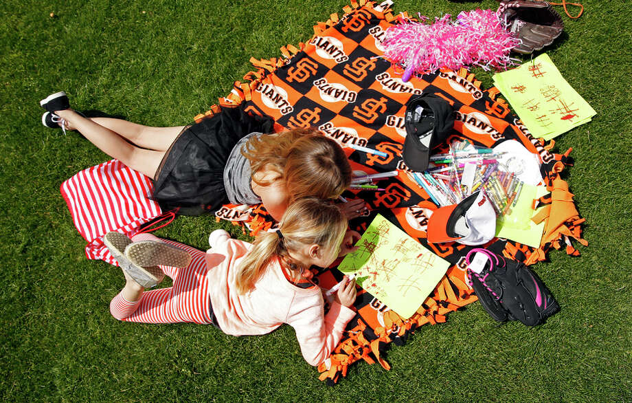 Giants fans Paige Talley, 7 (top), and Hayden Van Alen, 8, of Madera pass the time before the spring opener against the A's. Photo: Scott Strazzante / The Chronicle / ONLINE_YES