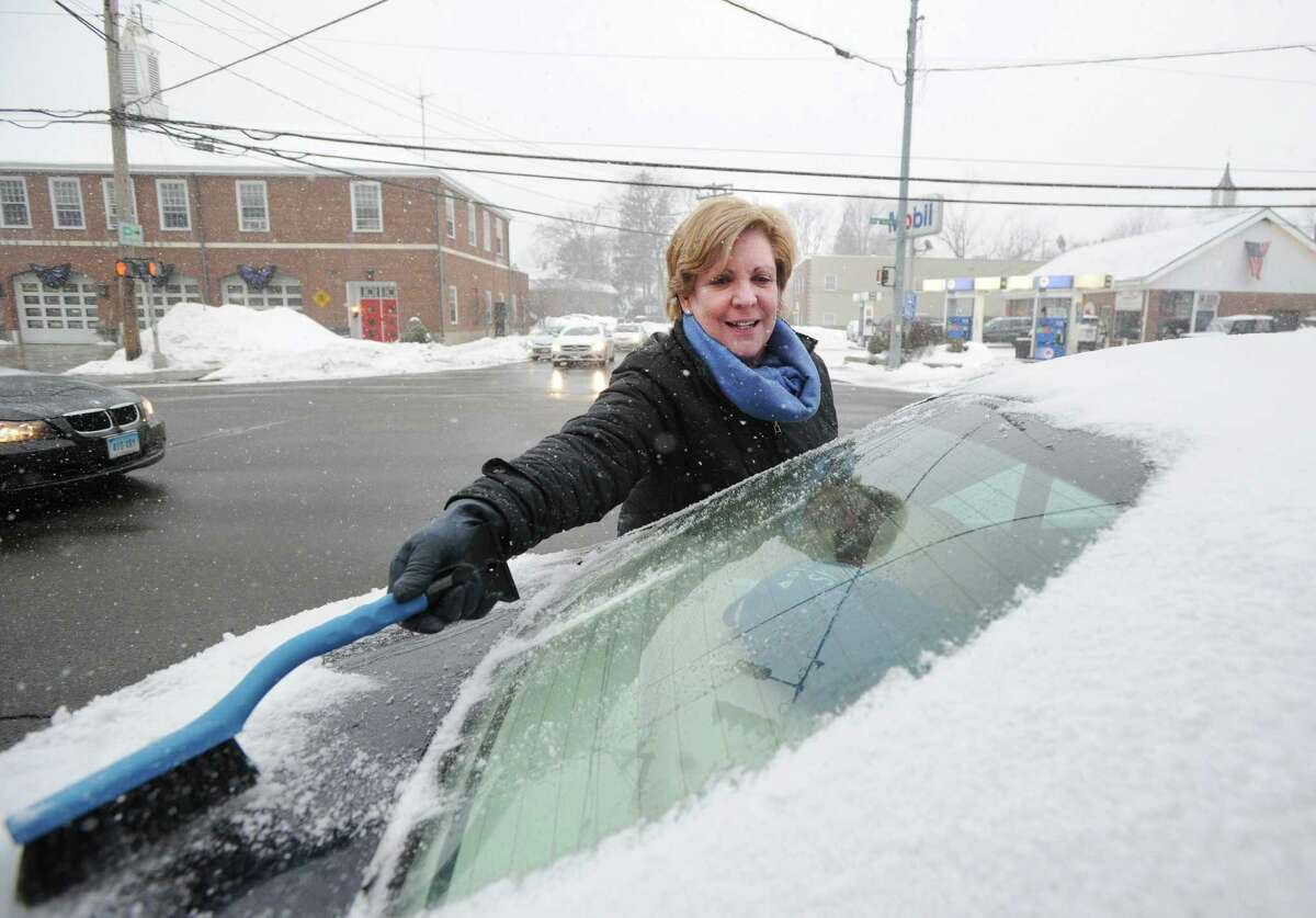 Joy Kruger of Old Greenwich clears snow from the back window of her car on Sound Beach Avenue during the start of the winter storm in Old Greenwich, Conn., Tuesday, March 3, 2015. The National Weather Service is calling for an accumulation of one inch of snow before a change-over to rain after midnight and rain throughout the day on Wednesday.