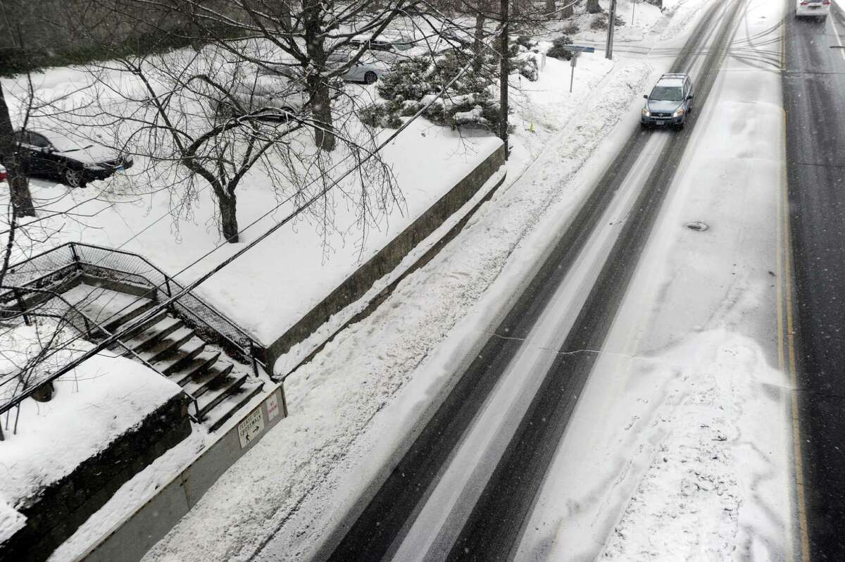 A car heads south on Sound Beach Avenue during the start of the winter storm in Old Greenwich, Conn., Tuesday, March 3, 2015. The National Weather Service is calling for an accumulation of one inch of snow before a change-over to rain after midnight and rain throughout the day on Wednesday.