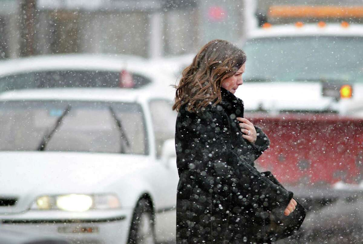 A woman grimaces as she crosses Sound Beach Avenue during the start of the winter storm in Old Greenwich, Conn., Tuesday, March 3, 2015. The National Weather Service is calling for an accumulation of one inch of snow before a change-over to rain after midnight and rain throughout the day on Wednesday.