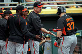 Manager Bruce Bochy and the Giants greet Adam Duvall after his second-inning home run off of the A's Rudy Owens.