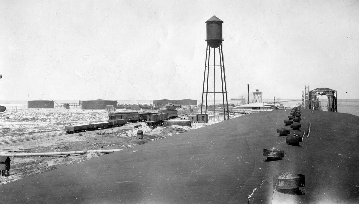 This1920sphoto documents the beginnings of oil tanks and a water tower from the roof of a warehouse at deep water.