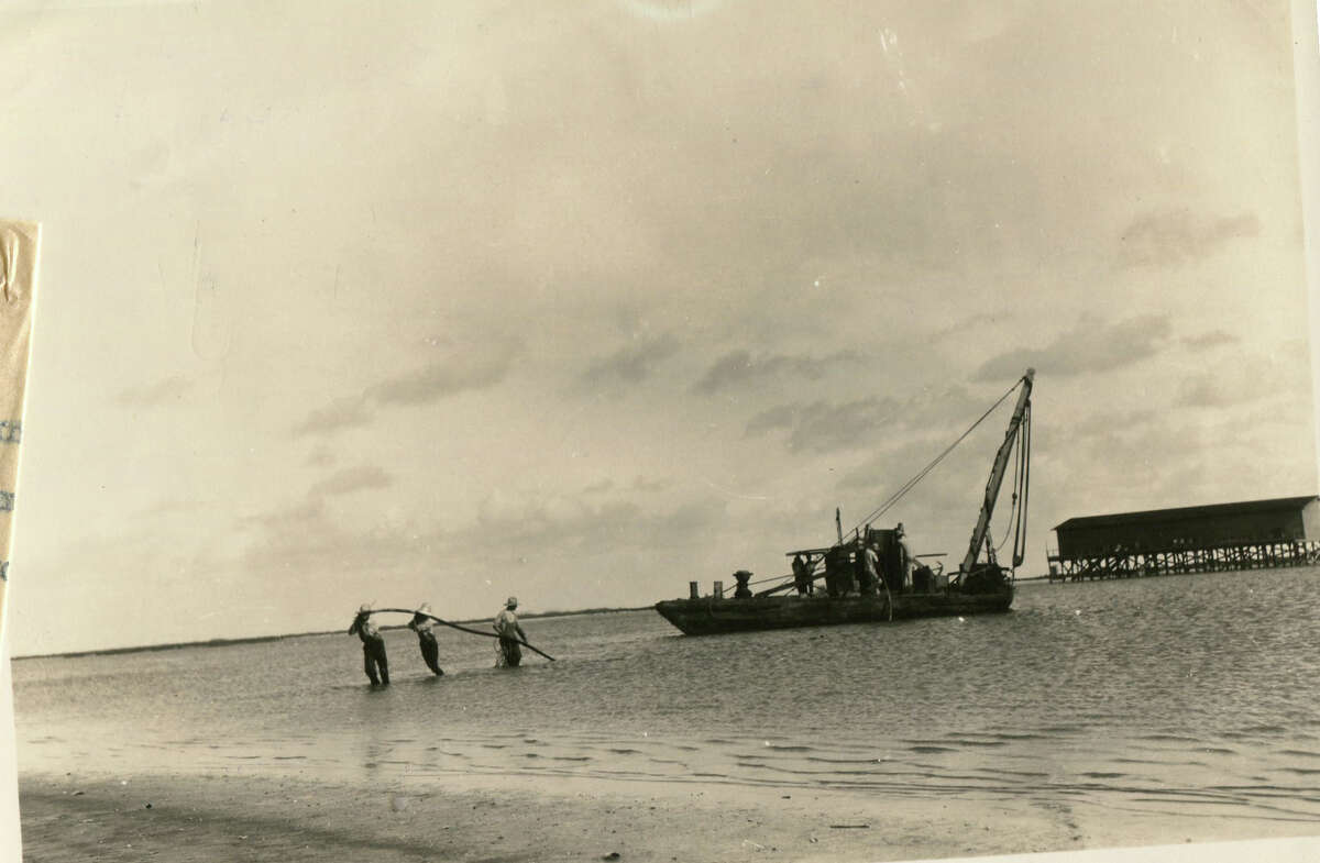 Workers lay the power and telephone cables across Corpus Christi Channel at Port Aransas.