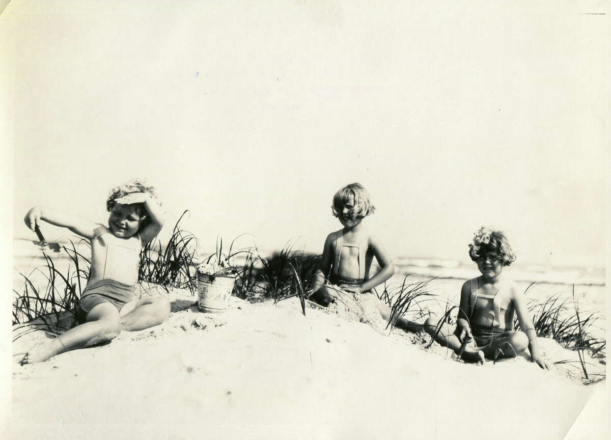 Children in their bathing suits play in the sand on the beach of Port Aransas.